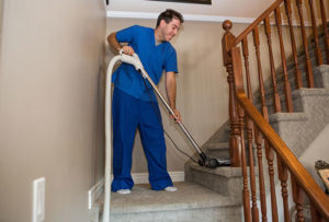Home Support for Elder Care. In-home support worked vacuuming the stairs.