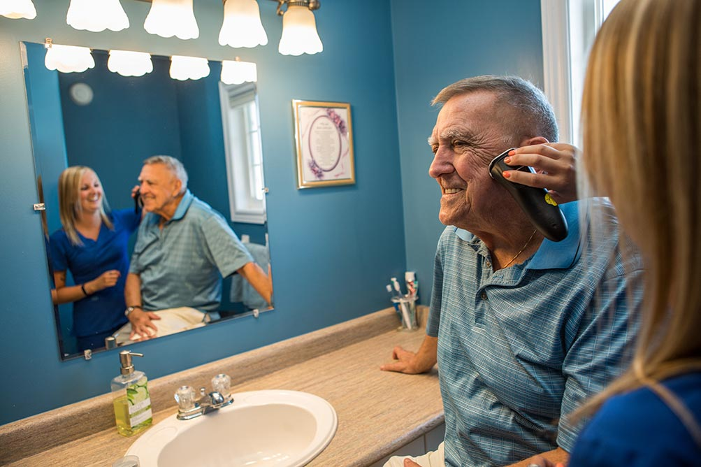 Caregiver helping shave elderly mans face