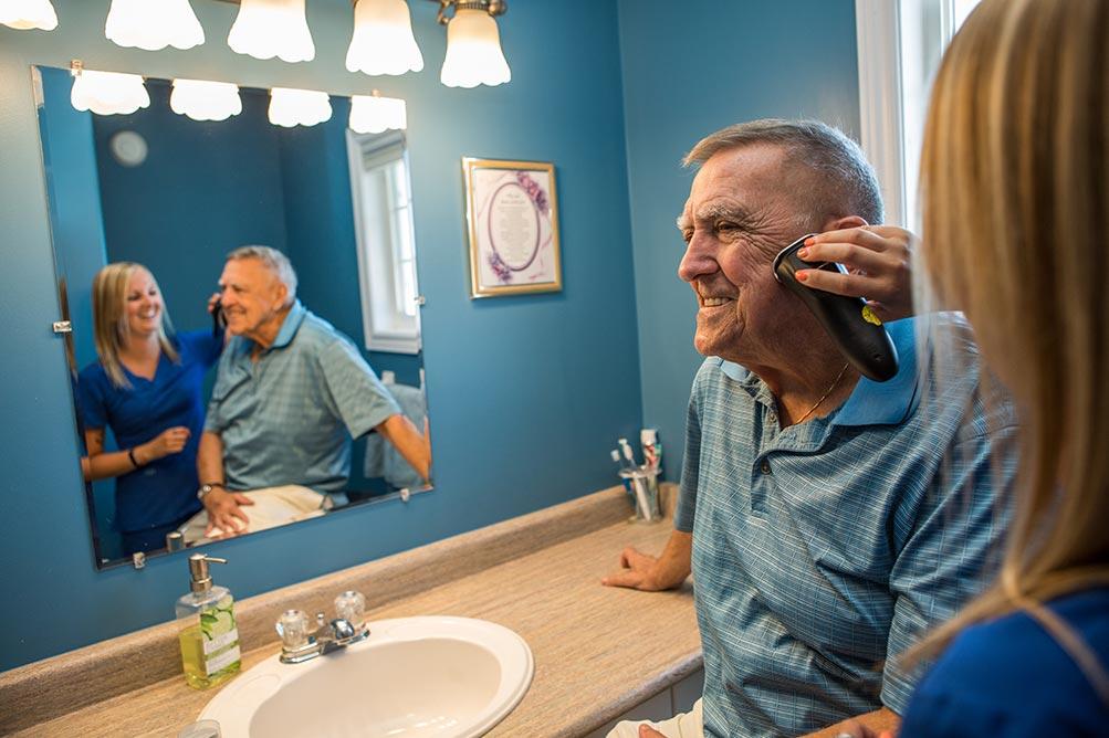 Caregiver helping shave elderly mans face