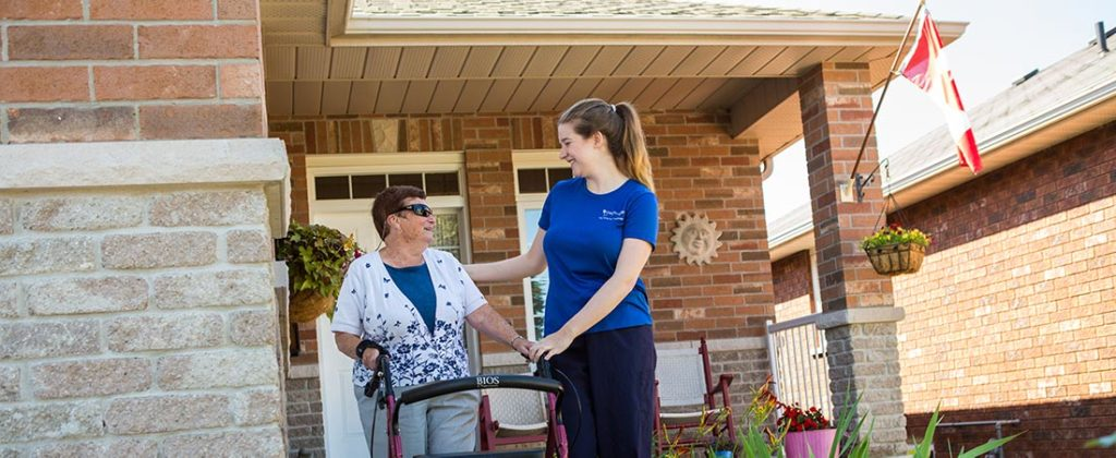Nurse helping an elderly woman walking down her front veranda