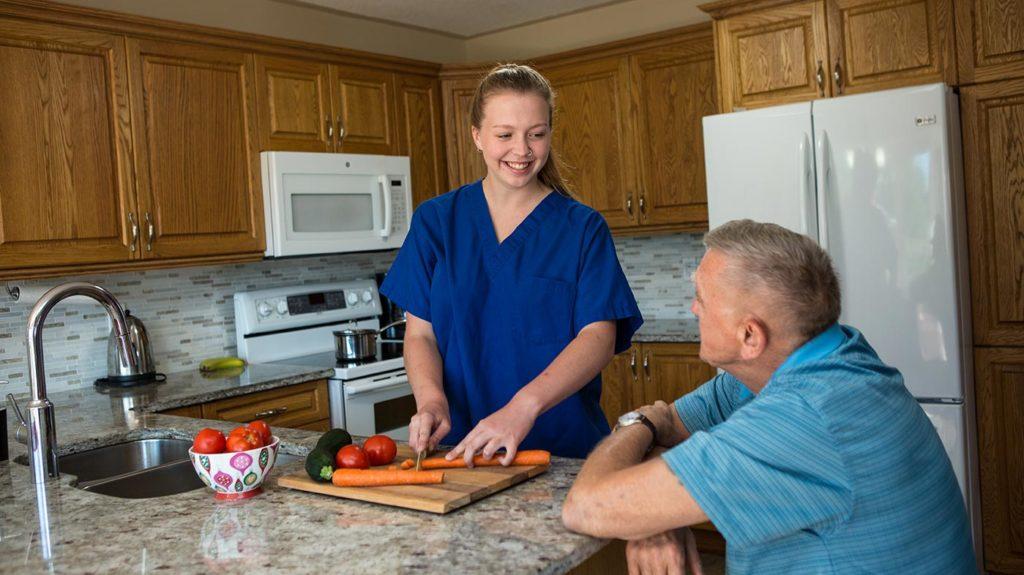 Caregiver preparing meal for elderly man