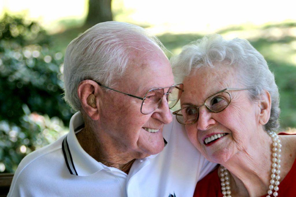 Elderly woman laying head on elderly mans shoulder