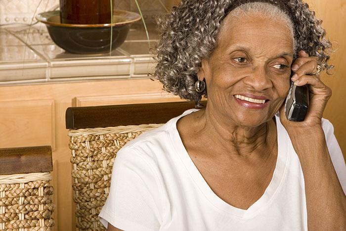 Elderly woman indoors using the phone