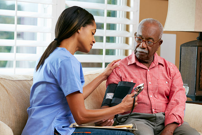 Female Nurse Visiting Senior Male Patient At Home
