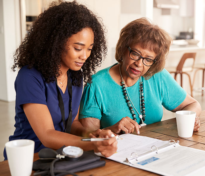 Female healthcare worker with a senior woman during a home health visi
