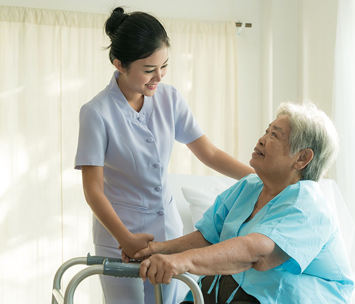 female nurse assisting elderly patient to walk
