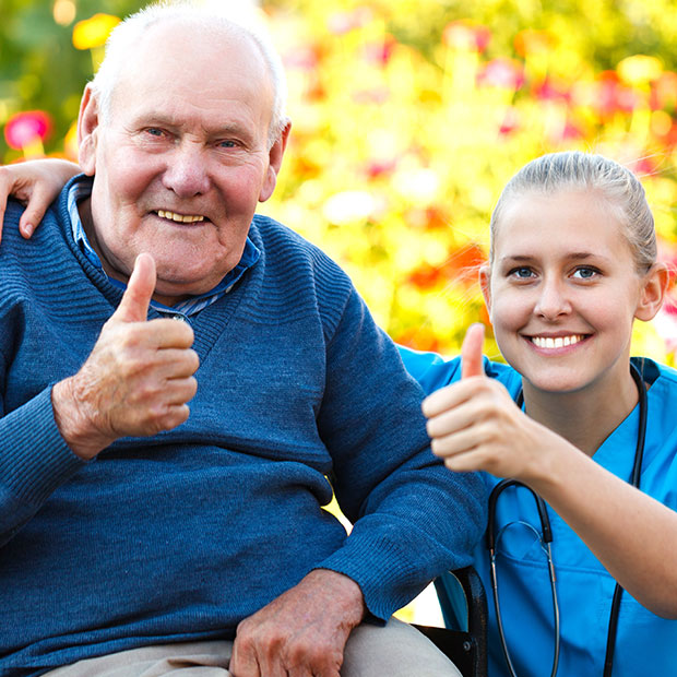 Elderly man and Caregiver smiling with their thumbs up