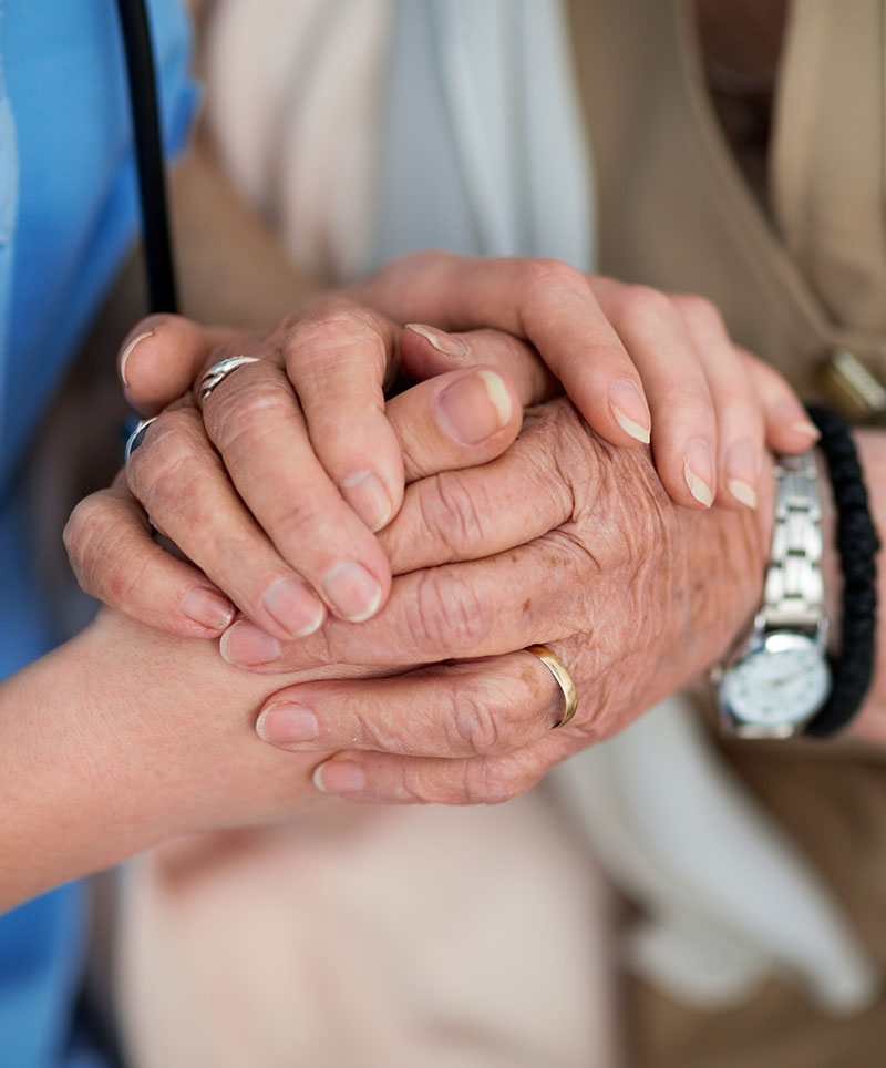Caregiver holding Elderly mans hand